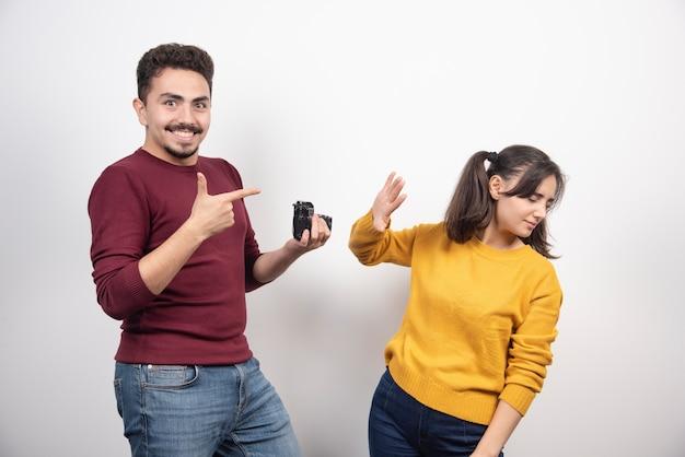 Linda pareja tomando fotografías con la cámara y posando sobre una pared blanca.