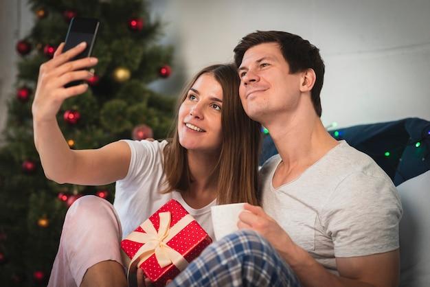Linda pareja tomando un selfie en la cama