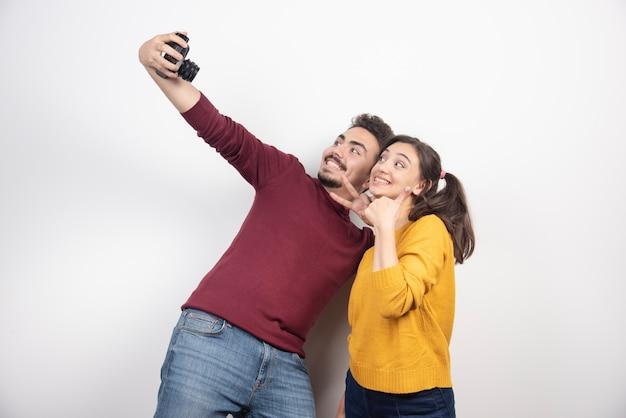Linda pareja tomando selfie con cámara y posando sobre una pared blanca. Foto gratis