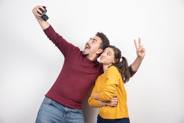 Linda pareja tomando selfie con cámara y posando sobre una pared blanca.
