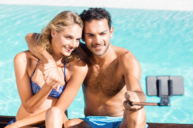 Linda pareja tomando selfie en la piscina
