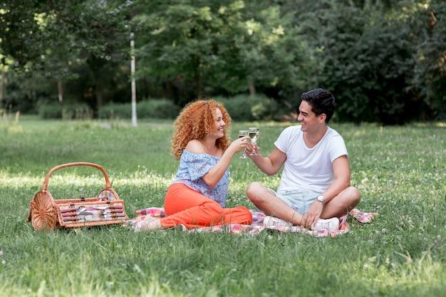 Linda pareja tostado mientras está sentado en una manta