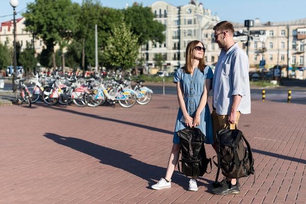 Linda pareja de turistas al aire libre con mochilas