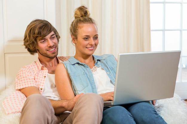 Linda pareja usando laptop sentado en el sofá de la sala de estar