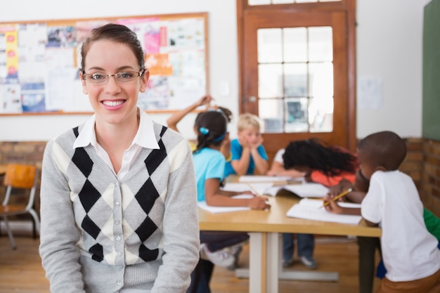 Linda profesora sonriendo a la cámara en la parte superior del aula