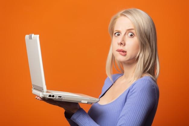 Linda rubia en blusa azul con ordenador portátil sobre un fondo de color naranja exuberante