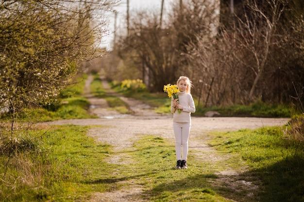 Linda rubia feliz niña con narcisos amarillos en el país de la primavera