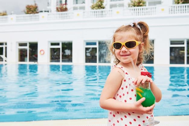 Linda rubia en la piscina y sosteniendo un cóctel infantil.