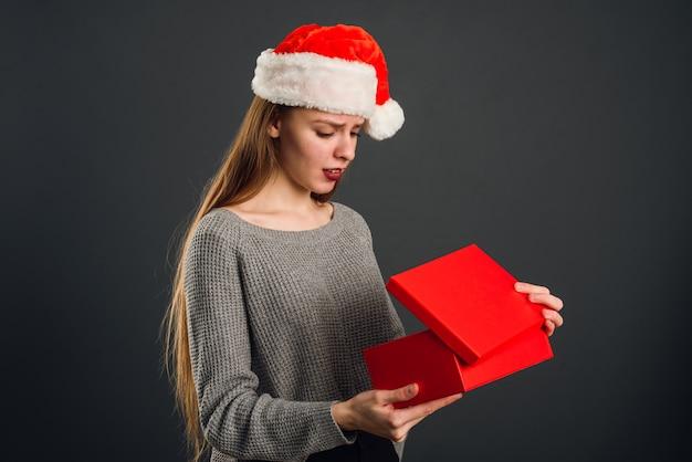 Linda rubia con sombrero de papá noel abre un regalo de año nuevo rojo para navidad.