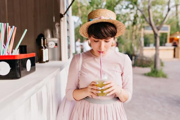Linda señorita de pelo corto con elegante manicura púrpura bebiendo cóctel verde de pie cerca del snack-bar