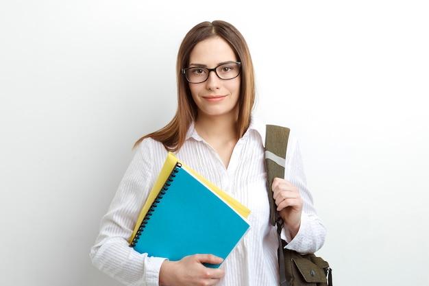 Linda sonriente joven estudiante con libros de texto