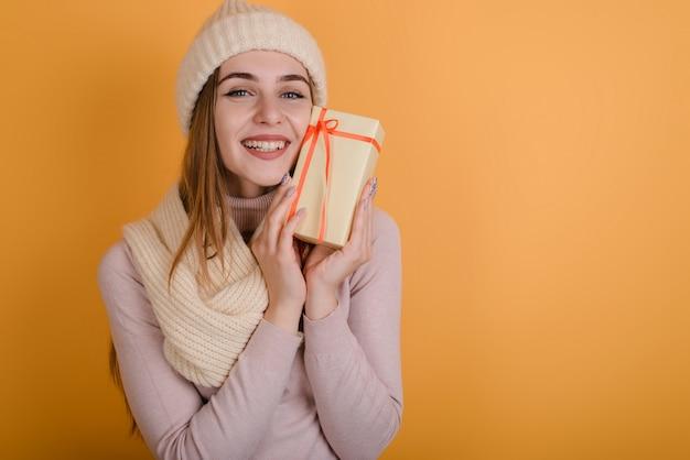 Linda y sonriente rubia con sombrero de punto está realmente feliz por su regalo