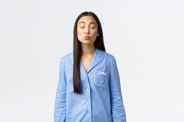 Linda tierna chica asiática en pijama azul que tiene un sueño romántico por la noche, cierra los ojos y besa a alguien, imagina a tu novio o cita, de pie fondo blanco, soñando despierto.