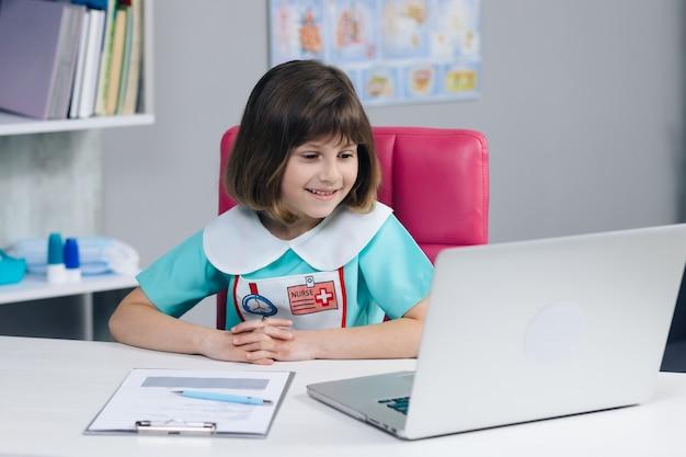 La linda vlogger de niña pequeña usa ropa médica hablando y grabando vlog para videoconferencia de blog de redes sociales