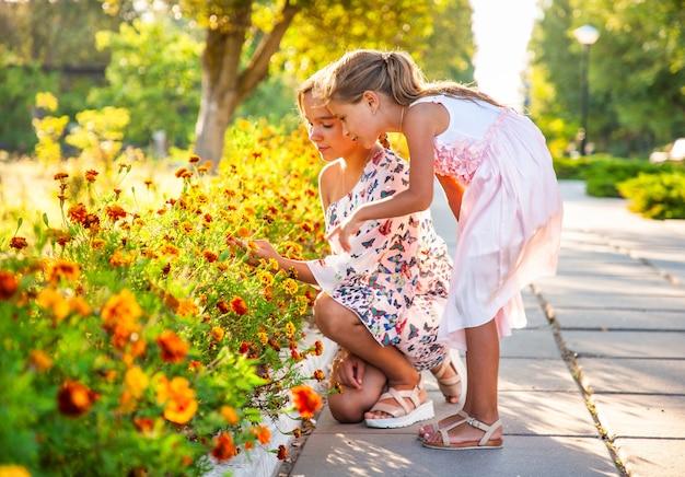 Lindas adorables chicas con delicados vestidos rosados huelen maravillosas caléndulas ardientes en un brillante parque de verano en un día soleado en unas tan esperadas vacaciones