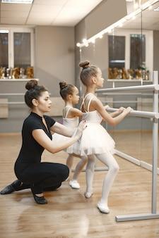Lindas bailarinas en traje de ballet rosa. niños con zapatillas de punta bailan en la habitación. niño en clase de baile con maestra.