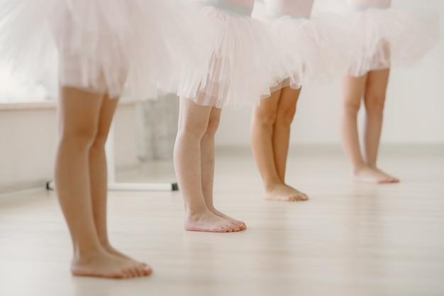 Lindas bailarinas en traje de ballet rosa. los niños con zapatos de punta bailan en la habitación.