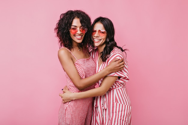Lindas chicas románticas se abrazan amistosamente. señoras con gafas de sol rosas riendo.