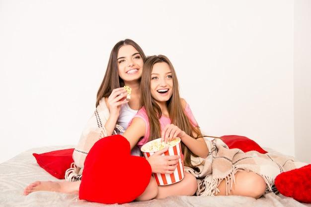 Lindas chicas sexy en pijama sentado en cuadros con palomitas de maíz
