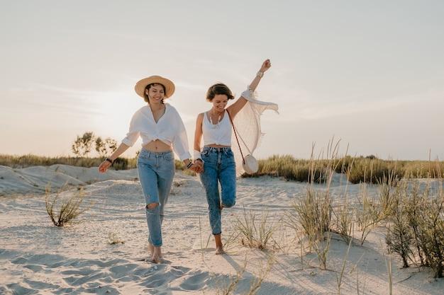 Lindas dos mujeres jóvenes divirtiéndose en la playa al atardecer, romance de amor lesbiano gay
