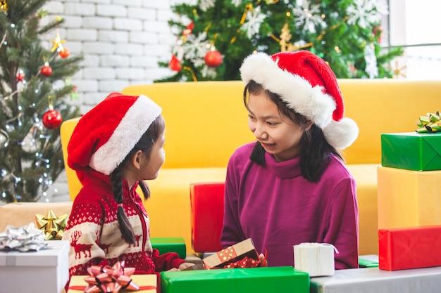 Lindas niñas asiáticas con cajas de regalo y decoración para celebrar el festival de navidad