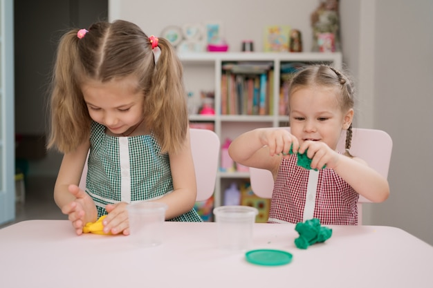 Lindas niñas moldeadas de plastilina en mesa rosa