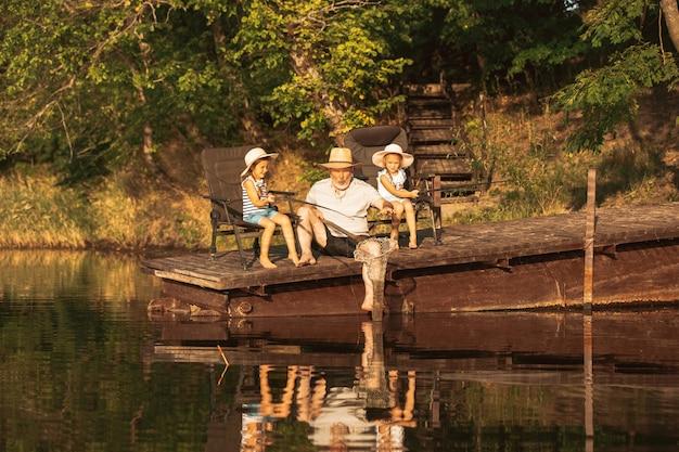 Lindas niñas y su abuelo están pescando en el lago o en el río. descansando en el muelle cerca del agua y el bosque en el atardecer del día de verano. concepto de familia, recreación, infancia, naturaleza.