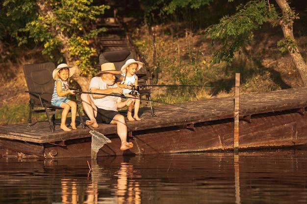 Lindas niñas y su abuelo están pescando en el lago o río.