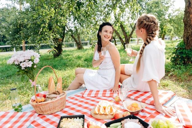 Lindas novias bebiendo champán en un picnic