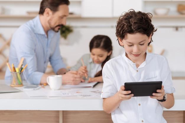 Lindo adolescente de cabello ondulado de pie frente a una encimera de la cocina y jugando en la tableta mientras su padre y su hermana hacen tareas en casa detrás