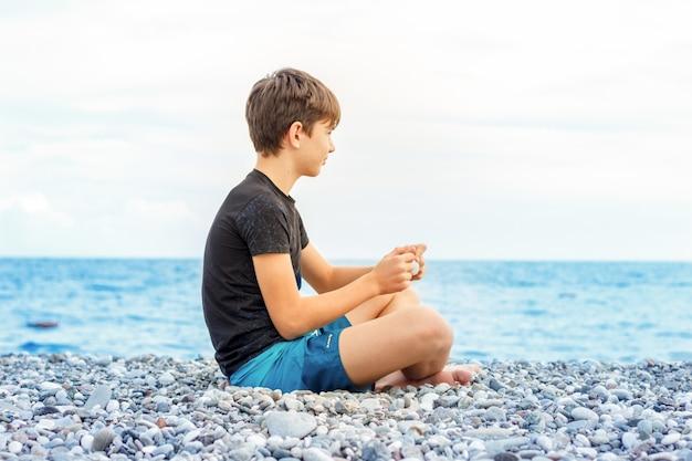 Lindo adolescente sentado en la playa y mirando el mar
