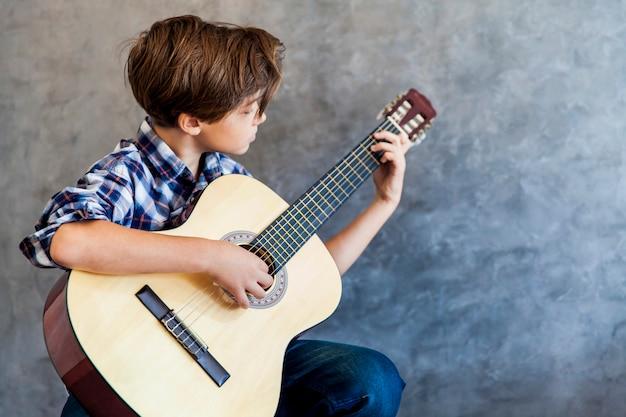 Lindo adolescente tocando la guitarra acústica