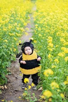 Lindo y alegre retrato de niño pequeño sentado en flores florecientes de diente de león en traje de abeja amarilla.