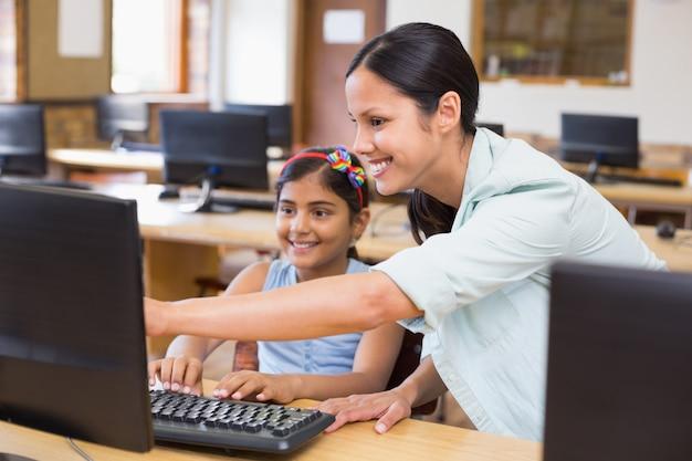 Lindo alumno en clase de informática con el maestro