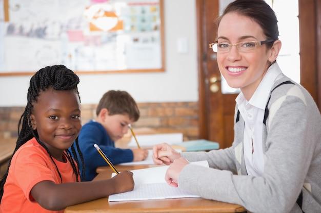 Lindo alumno recibiendo ayuda del maestro en el aula