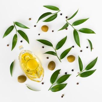 Lindo arreglo de vista superior de aceite de oliva y hojas