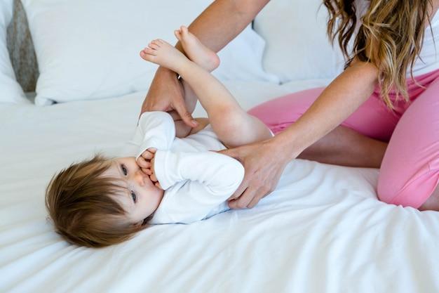 Lindo bebé acostado en una cama mientras su madre la abraza