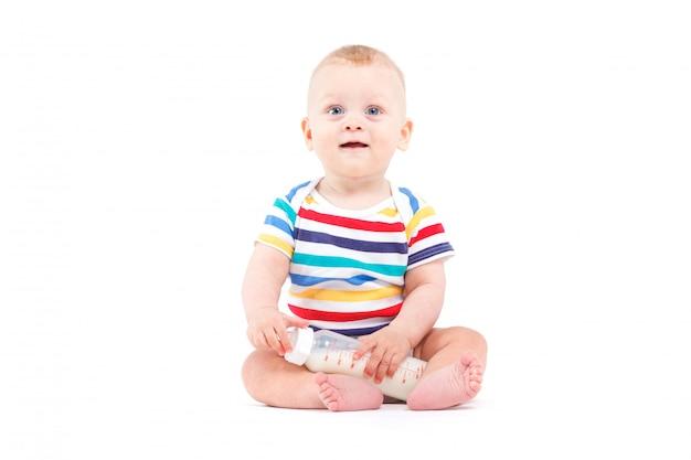 Lindo bebé alegre en camisa colorida sostenga la botella de leche