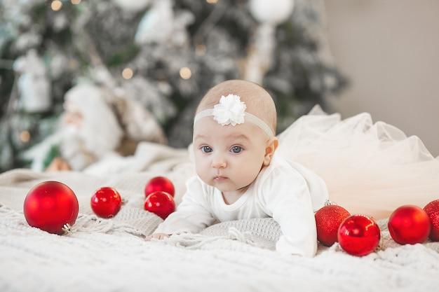 Lindo bebé con arbol de navidad
