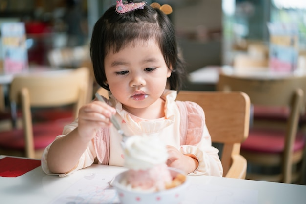 Lindo bebé asiático comiendo helado en la mesa del restaurante