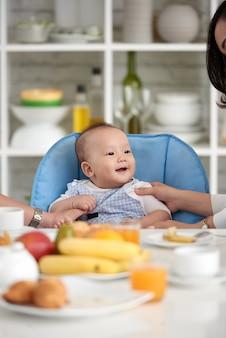 Lindo bebé asiático en mesa de comedor con familia