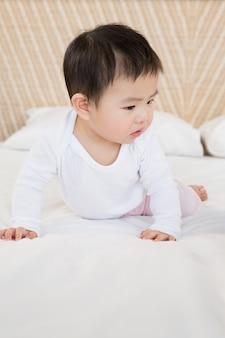 Lindo bebé en la cama mirando hacia abajo