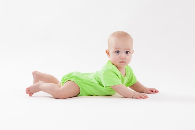 Lindo bebé curioso yace sobre su estómago