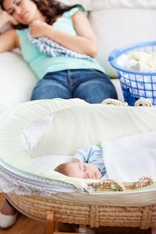 Lindo bebé durmiendo en su cuna con su madre acostada en el sofá en el fondo