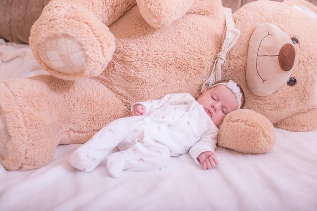 Lindo bebé durmiendo en pijama blanco con osito de peluche