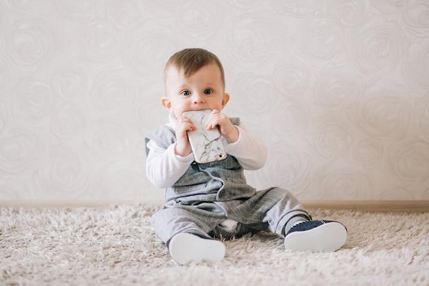Lindo bebé feliz en elegante traje de caballero sentado en blanco