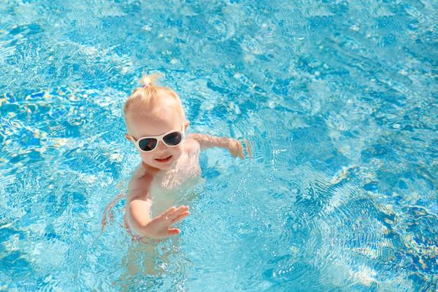 Lindo bebé en gafas de sol nadando en la piscina y agitando su mano.