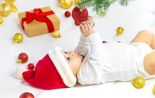 Lindo bebé con gorro de papá noel jugando con decoración navideña