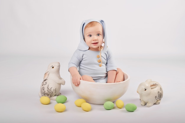 Lindo bebé gracioso con orejas de conejo y coloridos huevos de pascua y conejos. bebé de pascua saludo plantilla de tarjeta de pascua.