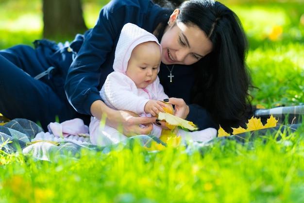 Lindo bebé jugando con una hoja de otoño mientras su madre la abraza en una manta en el parque